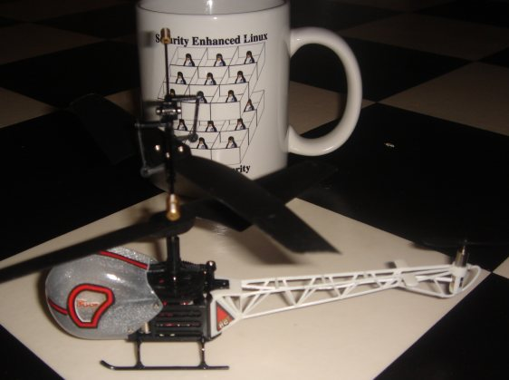 toy helicopter in front of SE Linux mug